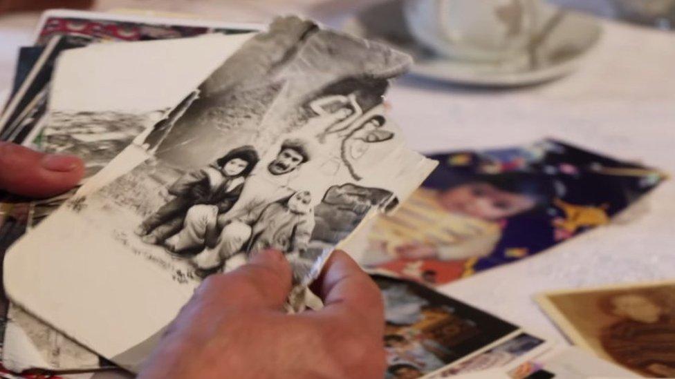 Старые черно-белые семейные фото на столе и в руках