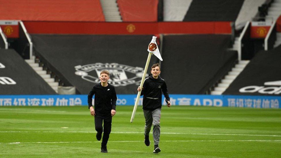 """Двое мальчиков на поле стадиона """"Олд Траффорд""""."""