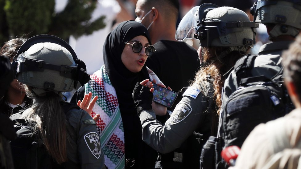 Israeli policewoman talks to a woman next to the Damascus Gate of Jerusalem's Old City (15 June 2021)