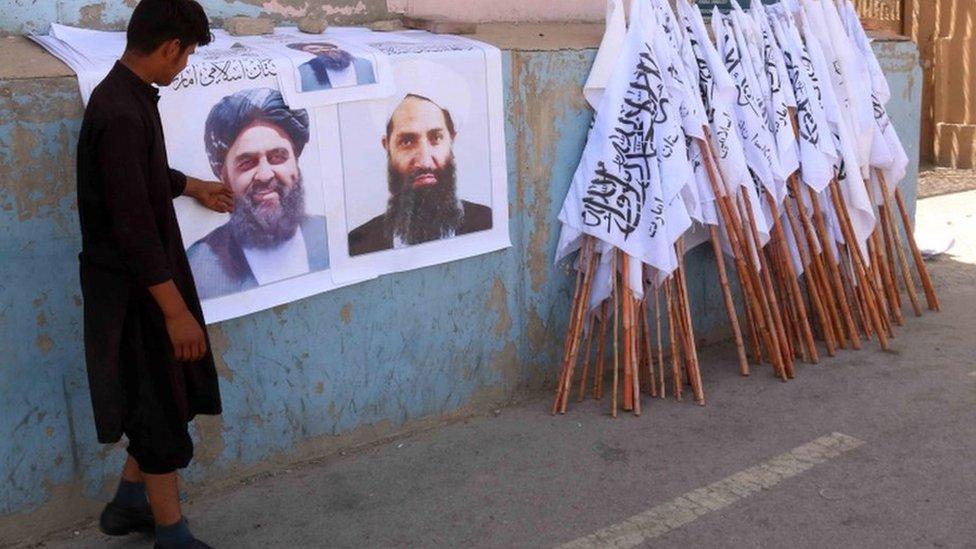 Плакаты с лидерами талибов и их флагом на улице Кабула