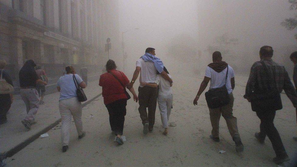 Бегущие по улице Нью-Йорка вблизи башен-близнецов в момент их обрушения