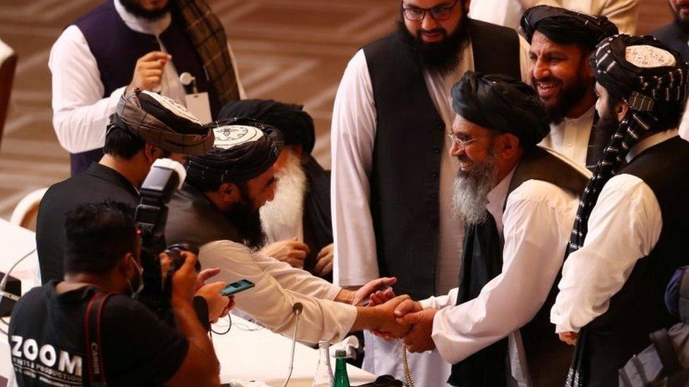 """Делегаты """"Талибана"""" пожимают друг другу руки во время переговоров между правительством Афганистана и Талибаном в Дохе, Катар (12 сентября 2020 г.)"""