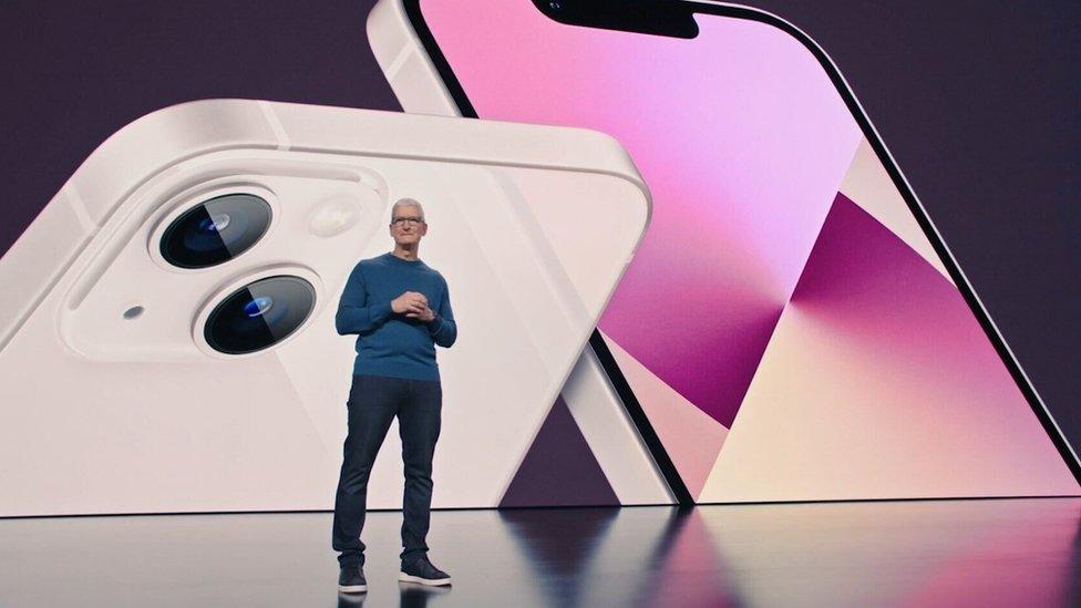 Глава Apple Тим Кук во время презентации на фоне снимка iPhone 13