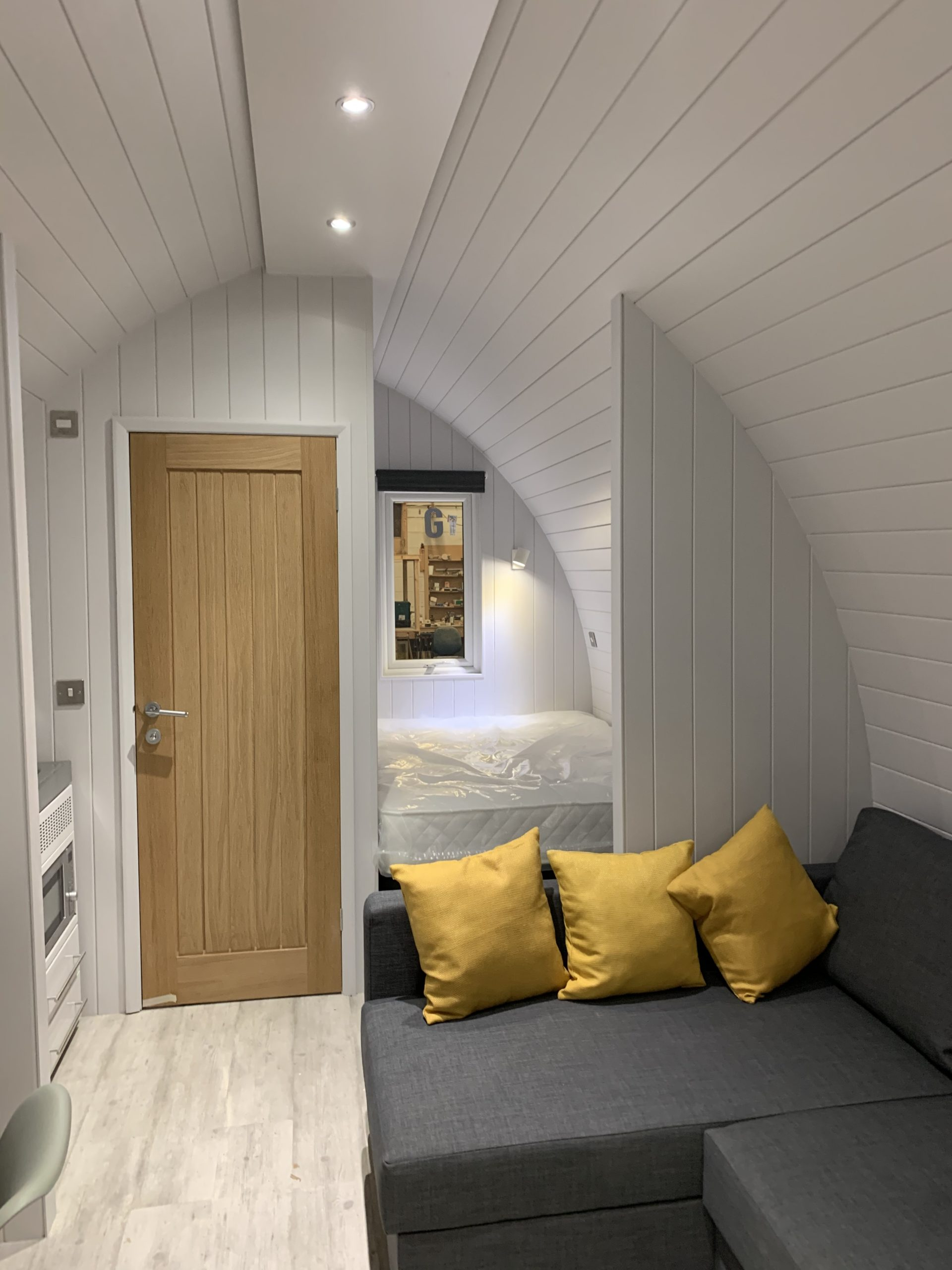 glamping pod interior shot of lounge and bedroom area with soft furnishings - glamping pods