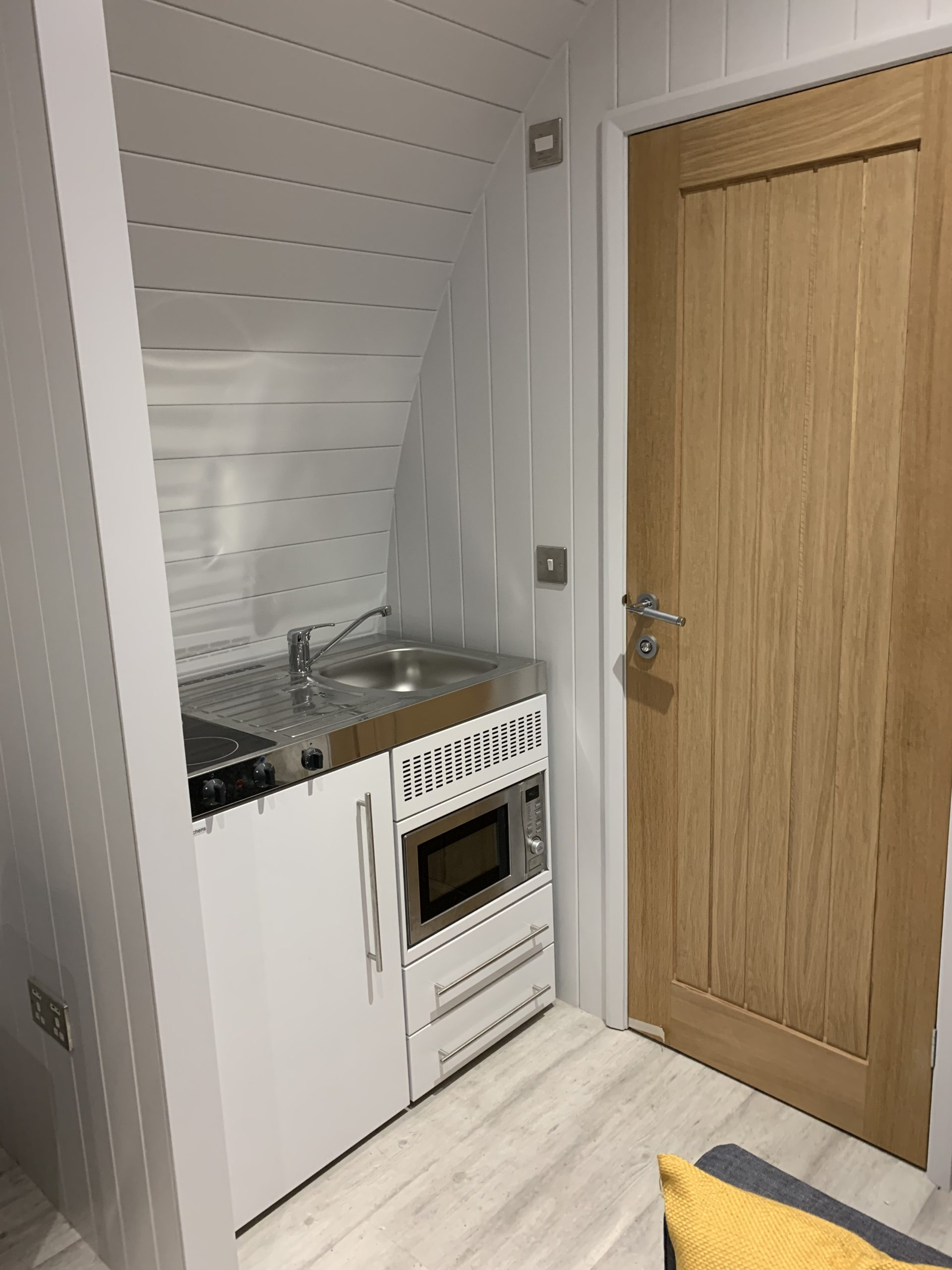 glamping pod interior shot of kitchen area with sink, hob and microwave - glamping pods for outdoor