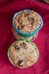 Three Whole Wheat Morning Glory Muffins in colorful paper liners stacked on a red napkin