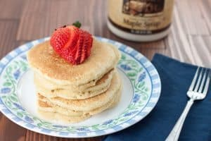 Plate of pancakes topped with strawberries with maple syrup in the background.