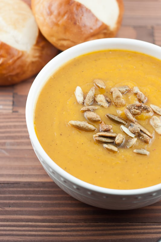 bowl of soup topped with roasted pumpkin seeds next to pretzel rolls