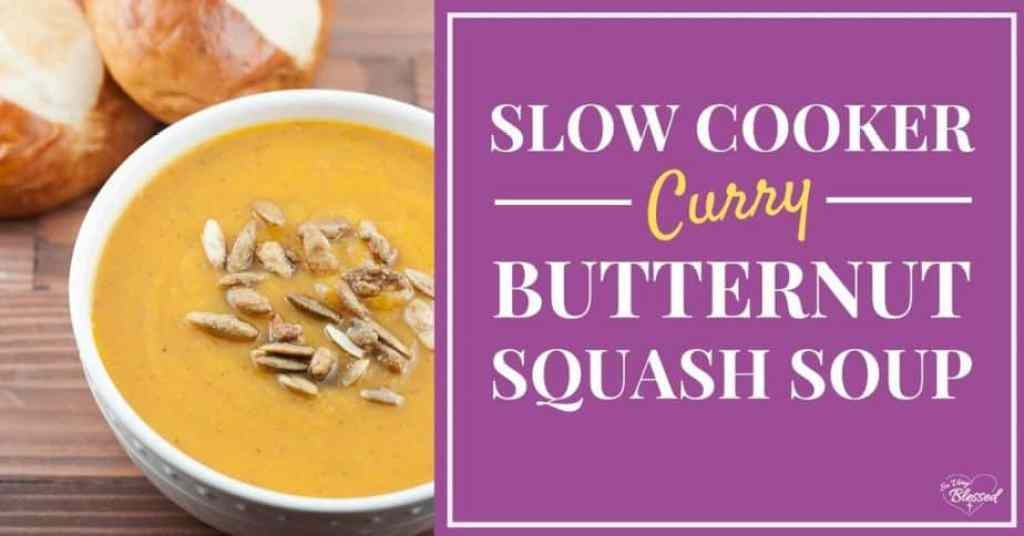Bowl of slow cooker curry butternut squash soup topped with roasted pumpkin seeds next to pretzel rolls