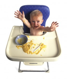 a baby sits in his high chair as tosses his baby food around