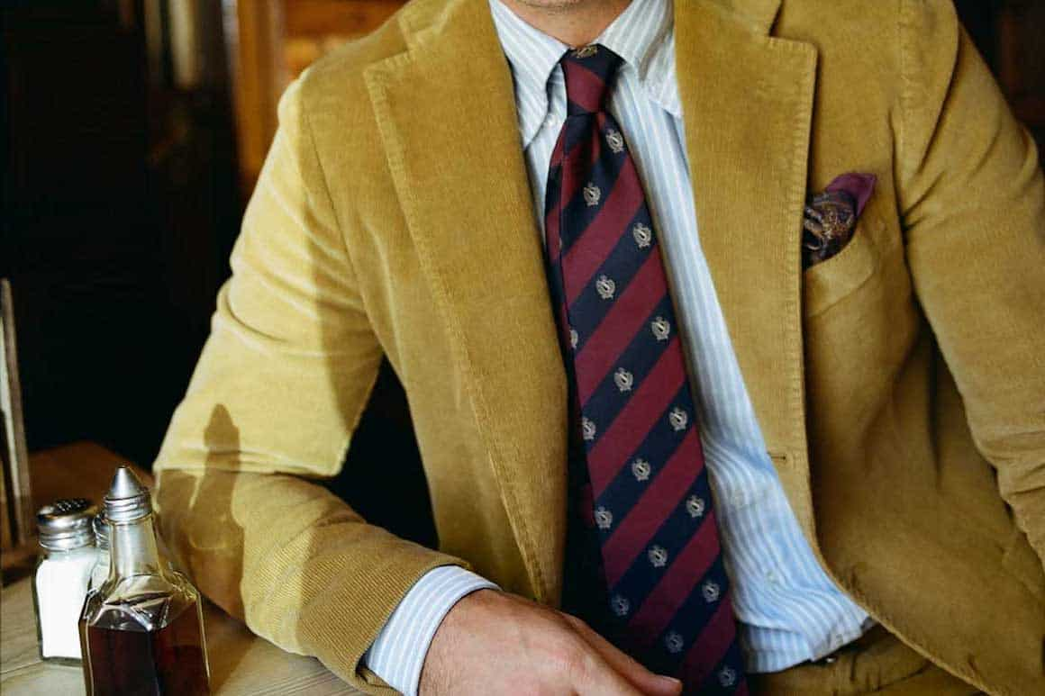 man wearing yellow suit with red striped tie