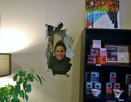 Lula Ruby owner Angela Favero shows just how large the hole that was hammered through her salon's wall during a late night weekend break-in.