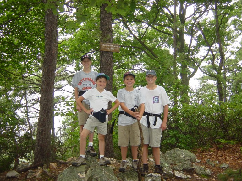 4 kids, each wearing hiking shoes, baseball caps and fanny packs, pose beneath the Center Point Knob sign.