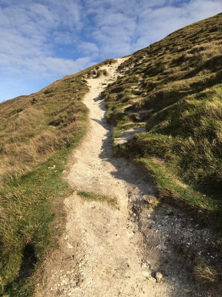 A steep sandy path bordered by green down grass appears to lead to the bright blue sky beyond.
