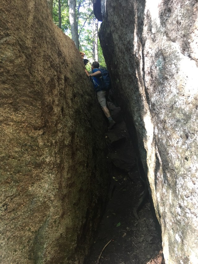A hiker steps side-ways to get through the crevice between large walls of rock