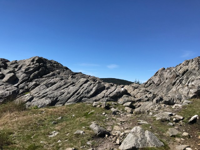 Large gray rock formations are a contrast to the bright blue sky