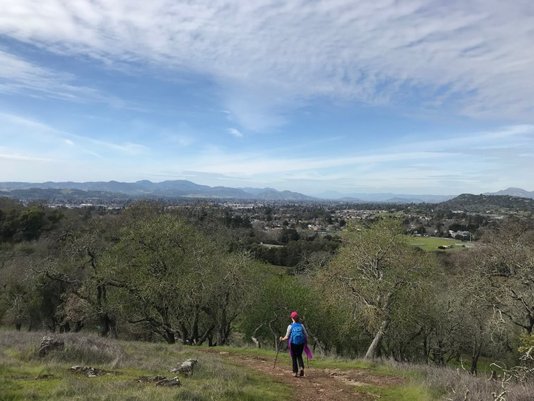 A hiker descending a trail toward a town, blue skies and mountains in the distance