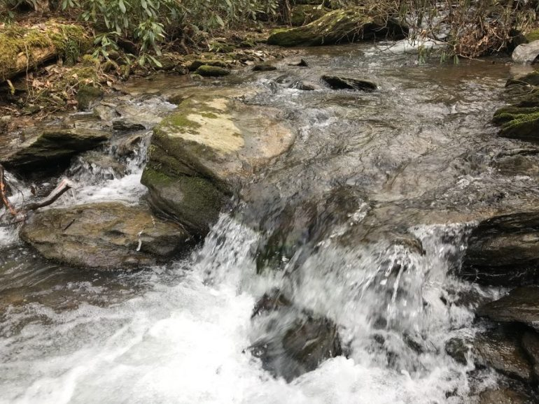 Rocks in a rushing stream create a bubbly waterfall