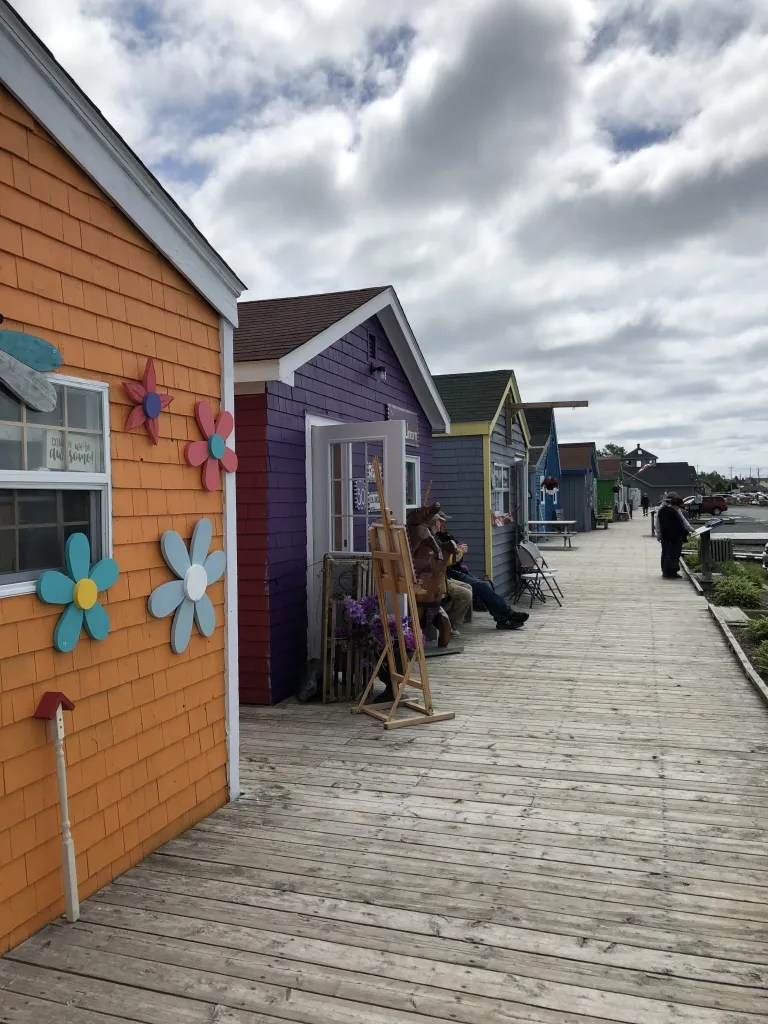 A boardwalk of brightly colored cottage styled shops