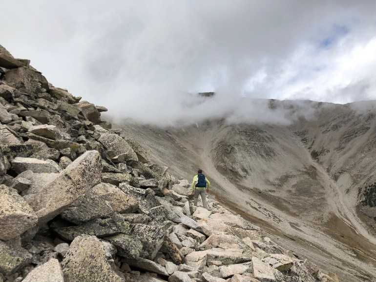 Gray clouds swirling over a Rocky Mountain top, a hiker walking over brown boulders toward the summit.
