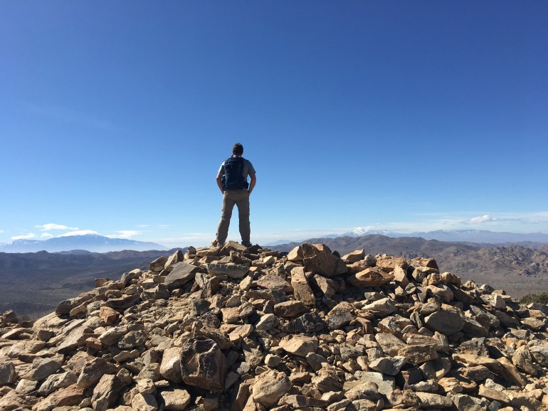 A man on a large rock pile at the top of a mountain