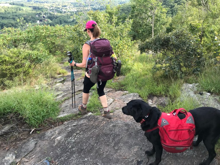 Female backpacker and black lab hiking dog walking down a Rocky Mountain summit