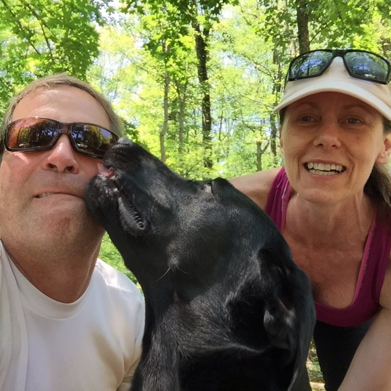 A black Labrador licking the face of a man in a selfie