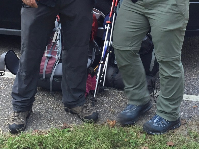 The legs and packs of 2 hikers