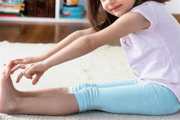 Toddler yogi in forward fold pose