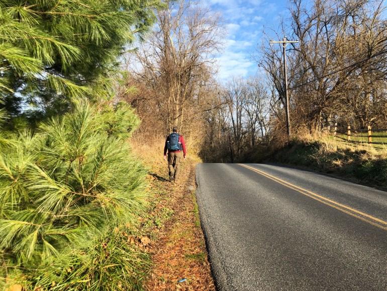 Backpacker walking along a road