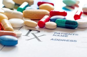 close up of a variety of prescription pills scattered over a prescription notepad