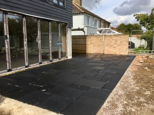 Read more about the article Huge rear patio in varying sized black sandstone