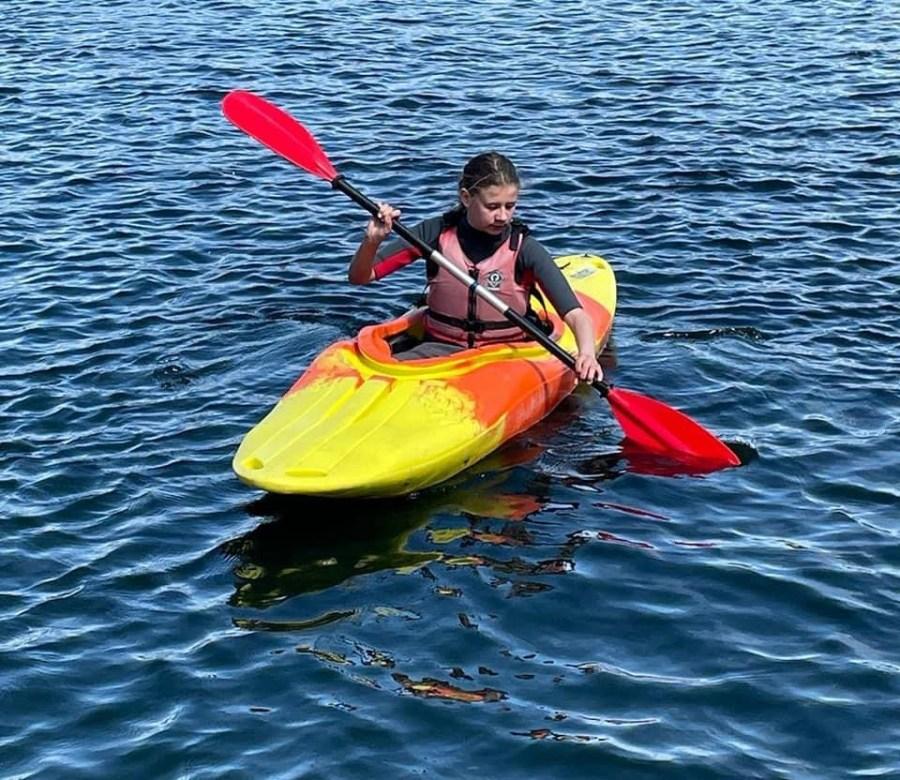 child paddling in canoe