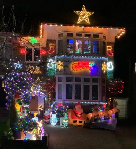 Christmas lights covering a house including a big bright star on the top and Father Christmas on his sleigh
