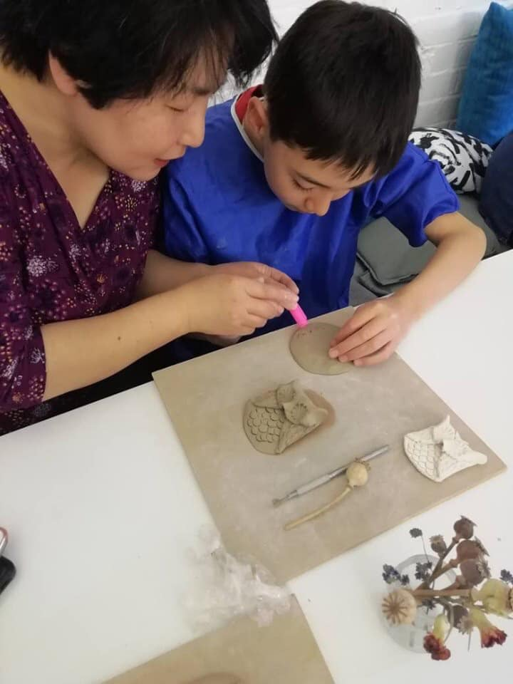 boy and mother creating clay artwork