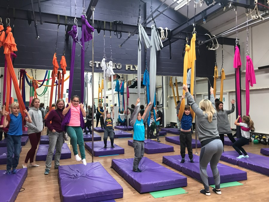 Children and young people practising their swinging skills at Studio Fly