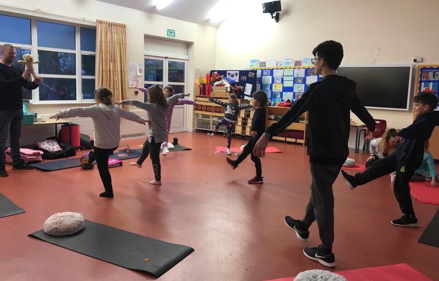 Children and young people balancing on one leg in a yoga lesson