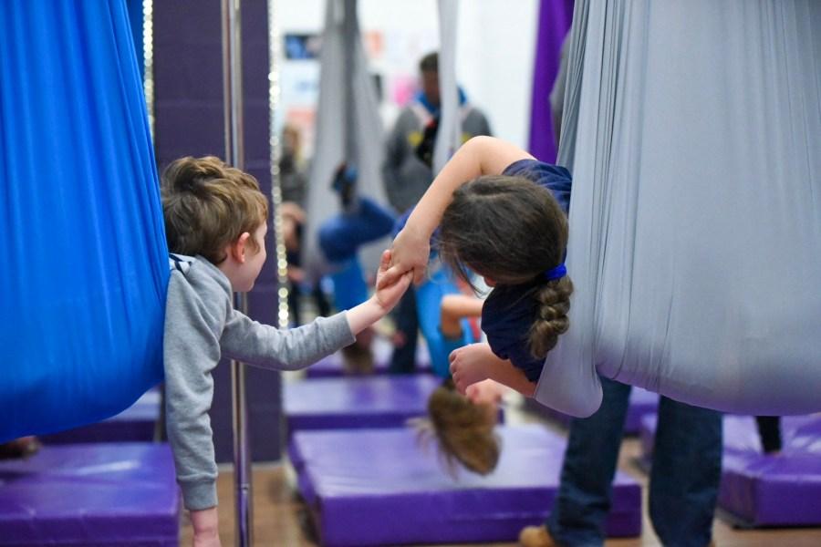 2 children holding hands across 2 yoga swings