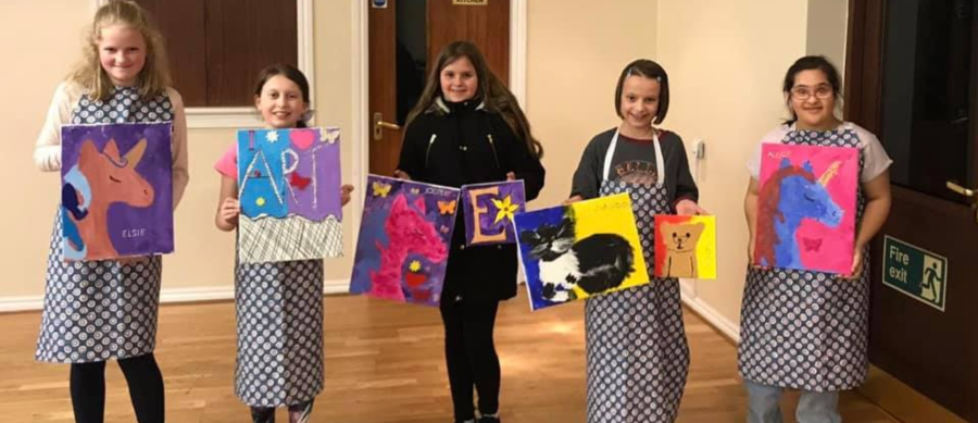 smiling young girls showing paintings