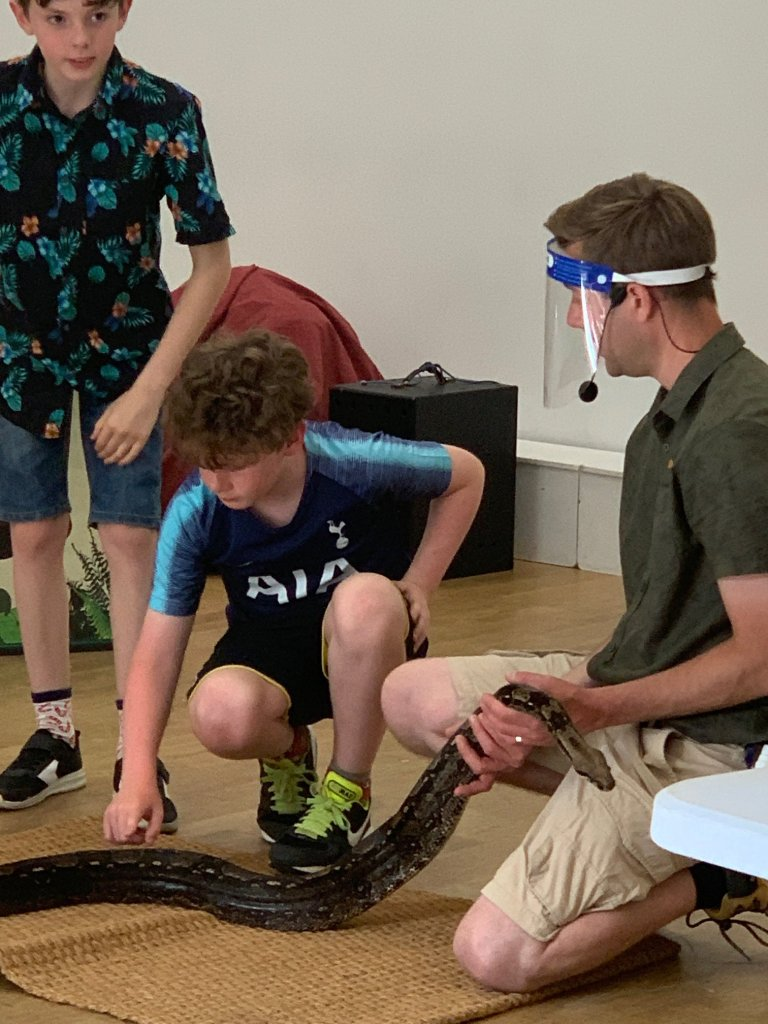 Boys touching a snake at SPACE's Ranger Stu event