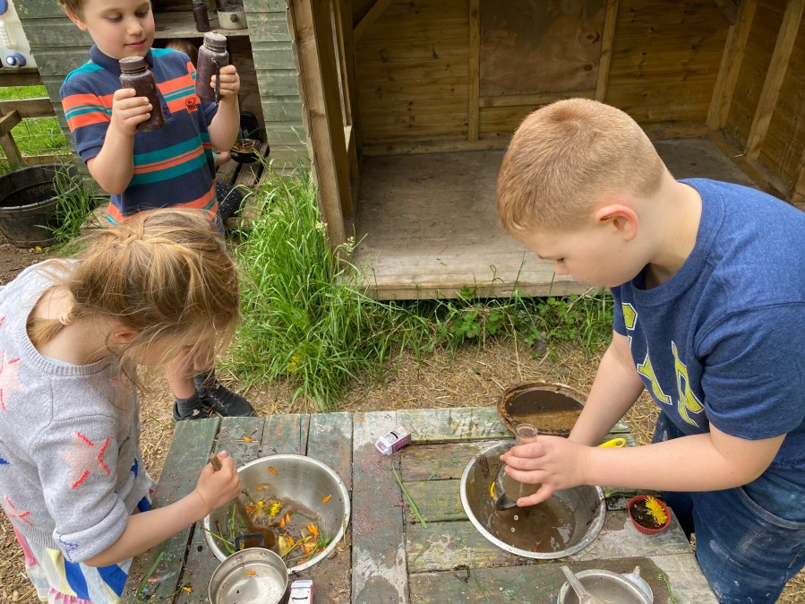 Children mixing potions in pans in a mud kitchen