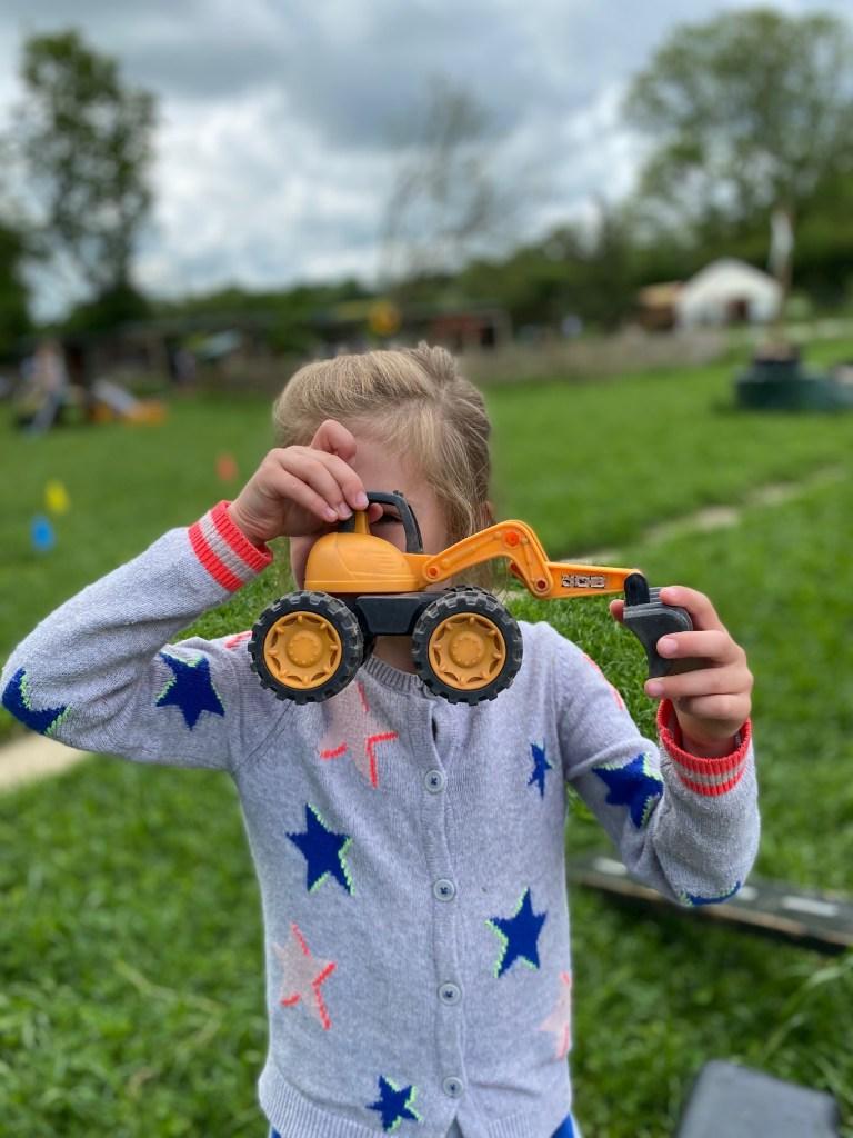 Girl peeking through a yellow toy digger