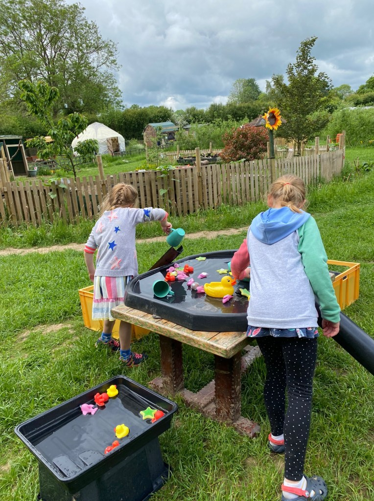 Two children playing with water toys in a tuff tray