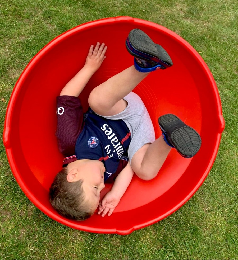 Boy lying down in a giant spinning top from Lending SPACE