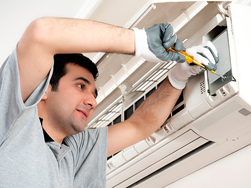 Commercial Building Maintenance image of an office maintenance engineer fixing an air conditioning unit