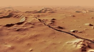An oblique view of a fracture in the orange bedrock of Mars running left to right along the middle horizon line.