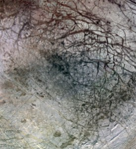 Cross cutting cracks and ridges of varying depths cover the surface of Europa, a moon of Jupiter.