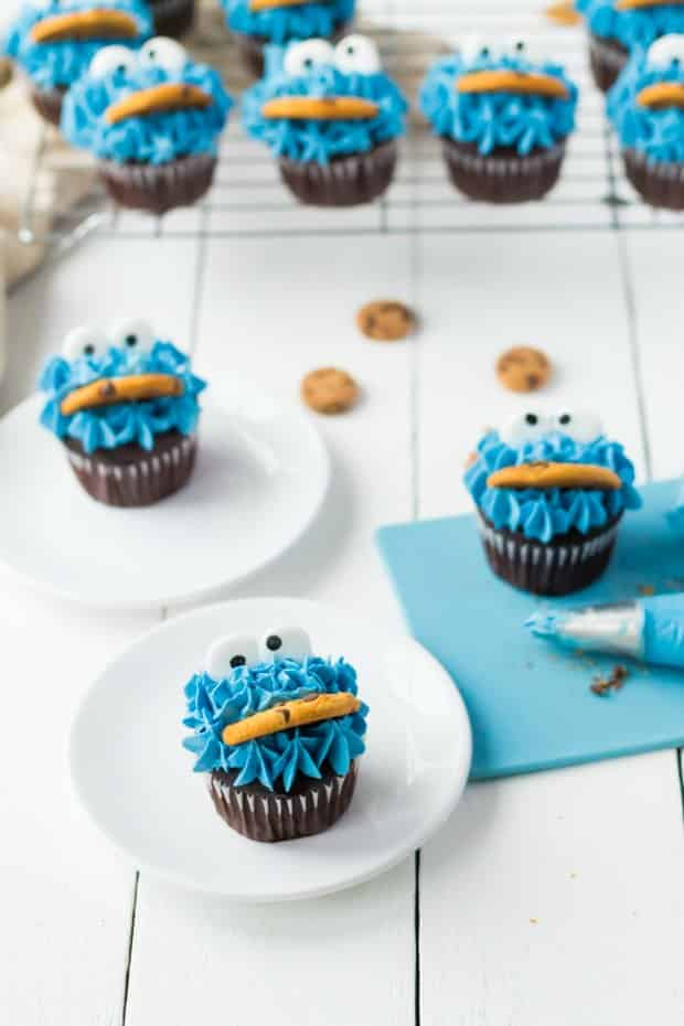 dozen cookie monster cupcakes being decorated