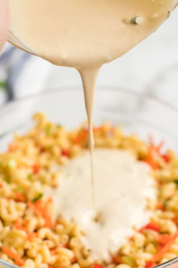 Cream Sauce Being Poured into Macaroni Pasta Salad