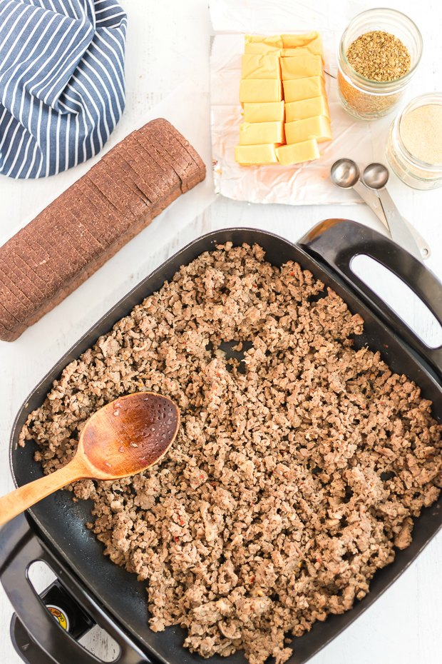 Ground beef in skillet to make hanky panky with velveeta and rye bread on the side